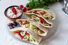 皮塔饼用烤鸡内圆角、新鲜的沙拉、黄瓜,甜辣椒粉、葱和酸奶sause填装了在白色 免版税库存照片