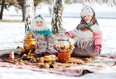 皮大衣和披肩的两个小女孩在他的头的俄国样式以俄国式茶炊为背景 免版税库存照片