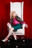 皮大衣的公主妇女坐王位 免版税图库摄影