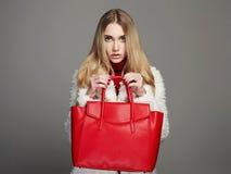 皮大衣的冬天美丽的妇女 秀丽时装模特儿女孩 有红色提包的豪华时髦的白肤金发的女孩 免版税库存照片