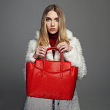 皮大衣的冬天美丽的妇女 秀丽时装模特儿女孩 有红色提包的豪华时髦的白肤金发的女孩 免版税库存图片