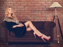 皮大衣的美丽的妇女坐沙发 免版税图库摄影