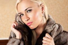 皮大衣的美丽的白肤金发的妇女 免版税库存图片