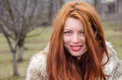 皮大衣的美丽的读的头发的女孩外面 库存照片