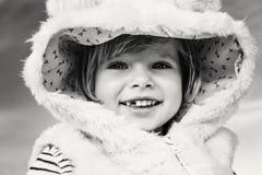 皮大衣的逗人喜爱的可爱的滑稽的微笑的笑的白种人孩子女婴 免版税库存照片