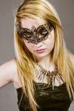 黑皮夹克、神奇面具和si的美丽的金发碧眼的女人 免版税库存图片