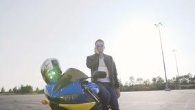 皮夹克和太阳镜的一个骑自行车的人,在日落,在摩托车旁边站立并且由电话讲话 股票录像