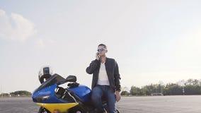 皮夹克和太阳镜的在他的摩托车旁边的骑自行车的人,在电话的立场和谈话 股票录像