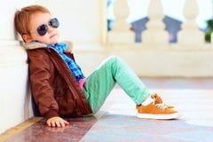 皮夹克和胶鞋子的逗人喜爱的时髦的男孩 免版税图库摄影