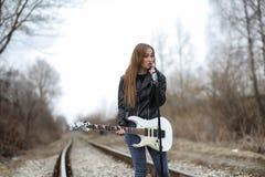 皮夹克的一个岩石音乐家女孩有吉他的 免版税库存照片