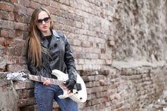 皮夹克的一个岩石音乐家女孩有吉他的 图库摄影
