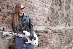 皮夹克的一个岩石音乐家女孩有吉他的 库存图片