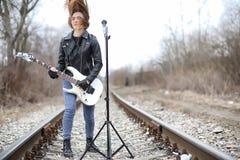 皮夹克的一个岩石音乐家女孩有吉他的 免版税库存图片