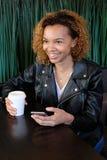 皮夹克的一个美丽的年轻深色皮肤的女孩有一个电话的在一只手上和有一杯的咖啡坐在桌上和 库存图片