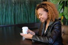 皮夹克的一个美丽的年轻深色皮肤的女孩有一杯的咖啡在她的手上坐在桌和微笑上看int 免版税库存照片
