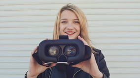 皮夹克的一个年轻时髦的金发碧眼的女人在水平的路辗盲人附近给照相机带来真正玻璃 股票视频