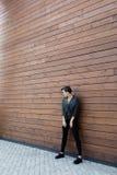 黑皮夹克的女孩在木墙壁附近 库存图片