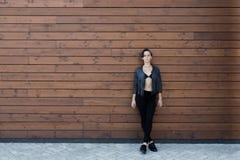 黑皮夹克的女孩在木墙壁附近 免版税库存照片