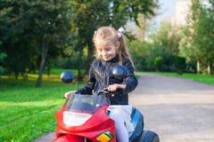 皮夹克的小女孩坐她的玩具 库存图片