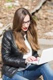 皮夹克的少妇使用膝上型计算机 免版税库存照片