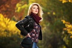 年轻皮夹克的时尚白肤金发的妇女在秋天公园 免版税库存照片