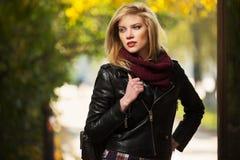 年轻皮夹克的时尚白肤金发的妇女在秋天公园 免版税图库摄影