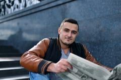 皮夹克的有袋子的微笑和读报纸的年轻人画象  免版税库存照片