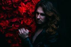 皮夹克的残酷人在与长的头发的一个赤裸身体在与红色花花的装饰附近站立 一孤独 库存图片