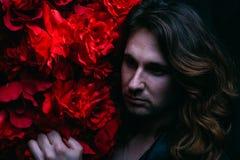 皮夹克的残酷人在与长的头发的一个赤裸身体在与红色花花的装饰附近站立 力量 免版税库存图片
