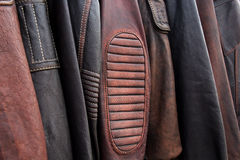 皮夹克的汇集在挂衣架的在商店 免版税库存图片
