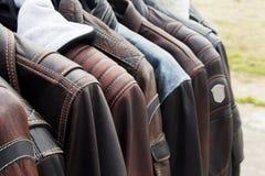 皮夹克的汇集在挂衣架的在商店 免版税库存照片