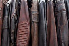 皮夹克的汇集在挂衣架的在商店 免版税图库摄影