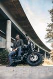 皮夹克的男性骑自行车的人在桥梁附近的一辆摩托车 库存图片