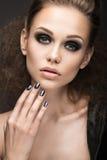 皮夹克的美丽的女孩有明亮的构成和修指甲猫眼的 秀丽表面 钉子设计 库存图片