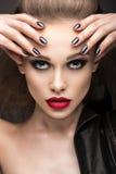 皮夹克的美丽的女孩有明亮的构成和修指甲猫眼的 秀丽表面 钉子设计 库存照片