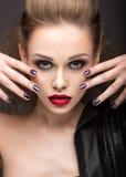皮夹克的美丽的女孩有明亮的构成和修指甲猫眼的 秀丽表面 钉子设计 免版税图库摄影