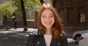 皮夹克的美丽的姜女孩愉快地微笑入照相机和修理她的在活跃城市街道背景的头发 股票录像