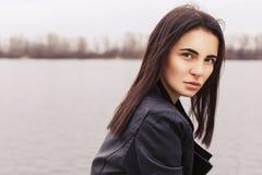 黑皮夹克的美丽的深色的妇女坐 免版税库存照片