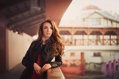 皮夹克的美丽的红发女孩在都市风景 免版税库存图片