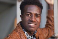 皮夹克的英俊的确信的微笑的年轻黑人 免版税图库摄影