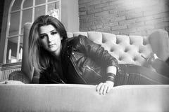 皮夹克的迷人的女孩有说谎在沙发的高泵浦的 库存照片