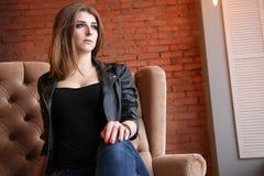 皮夹克的迷人的岩石女孩坐沙发 免版税图库摄影