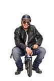 皮夹克的骑自行车的人坐一辆小自行车 免版税图库摄影