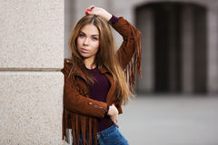 皮夹克的年轻时尚妇女在城市街道上 免版税库存图片