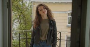 皮夹克身分的俏丽的深色的女孩在阳台有绿色城市视图微笑入照相机的是高兴和愉快的 影视素材