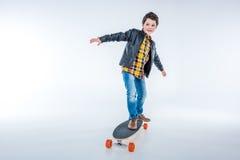 皮夹克骑马滑板的男孩在灰色 图库摄影