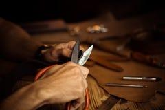 皮带的运作的过程在皮革车间 举行制作工具和工作的人 老的坦纳 免版税库存图片