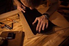 皮带的运作的过程在皮革车间 举行制作工具和工作的人 老的坦纳 库存图片