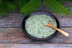 皮肤海盐与杉木集中在一个黑圆的盘和木匙子的补品在与冷杉branc的老木背景 免版税库存照片