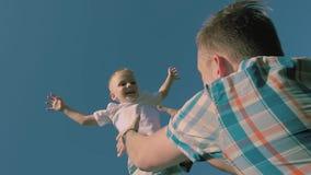 年轻皮肤白皙的父亲特写镜头在天空中的投掷他的儿子 股票录像